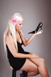 Pretty girl in a black dress holding her shoe. stock image