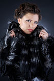 Pretty girl in a black fur coat Royalty Free Stock Image