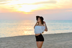 Pretty girl in black hat and shirts on sunset Stock Image