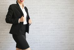 Pretty girl in black suit standing and smiling in her office. body part royalty free stock photos