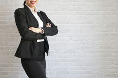 Pretty girl in black suit standing and smiling in her office. body part stock image