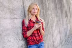 Pretty girl with blonde hair, big hazel eyes, with a cup in her hands is having a break from work. She is dreaming about the weeke. Nd royalty free stock image
