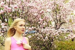 Pretty girl hold magnolia flower at blossoming tree, spring garden. Pretty girl with blonde hair and red lips hold magnolia flower at blossoming tree in spring stock photography