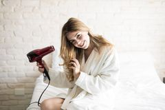 Pretty girl blow drying her hair. Portrait of a gorgeous young Hispanic woman in a bathrobe using a blow dryer while sitting on her bed in the morning Stock Photos