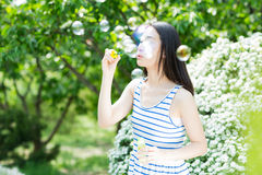 Pretty girl blowing bubbles Stock Photos