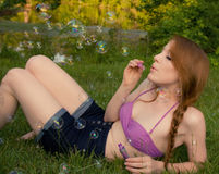 Pretty Girl Blowing Bubbles. A picture of a gorgeous young woman in shorts and a bikini top blowing bubbles outside Royalty Free Stock Photos