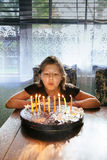 Pretty girl blowing the candles on the cake Stock Photography