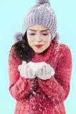 Pretty girl blowing snow from her hands on studio stock images