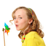 Pretty girl blowing windmill. Pretty child showing energy saving concept blowing windmill Royalty Free Stock Photos