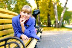 Pretty girl in blue coat on bench Stock Photo
