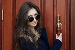 Pretty girl in blue coat and black glasses Stock Photos