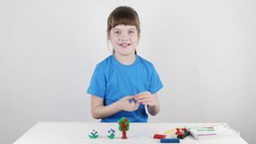 Pretty girl in blue molds from plasticine on white table. In white room stock footage