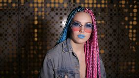 Pretty girl is looking at camera. Pretty girl with blue and pink dreadlocks is looking at camera standing outside stock footage