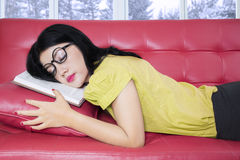 Pretty girl with book napping on sofa Royalty Free Stock Photos