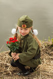 Pretty girl with a bouquet of flowers sitting by the river in uniform on the day of victory in sorrow. Pretty girl with a bouquet of roses in a military uniform Stock Image