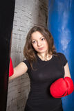 Pretty girl boxing pear. She fulfills blows in the gym Royalty Free Stock Images