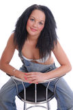 Pretty girl in bra and dungarees on stool Stock Image