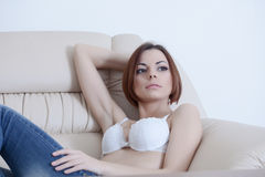 Pretty girl in bra and jeans sit on sofa Stock Photography