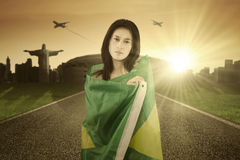 Pretty girl with Brazilian flag on the road Royalty Free Stock Photos