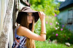 Pretty girl in brown hat sitting beside old wooden Stock Photos