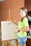 Pretty girl with brushes standing  near easel Royalty Free Stock Image