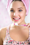 Pretty girl brushing her teeth in front of mirror Stock Photos