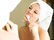 Pretty girl brushing teeth Stock Images