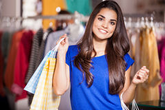 Pretty girl buying some clothes. Cute young woman carrying some shopping bags and doing some shopping in a clothing store Stock Photo