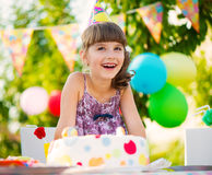 Pretty girl with cake at birthday party Stock Images