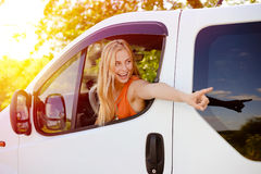 Pretty girl in car excited pointing at something Royalty Free Stock Image