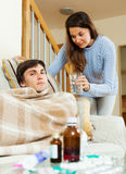 Pretty girl caring for sick husband Stock Photo