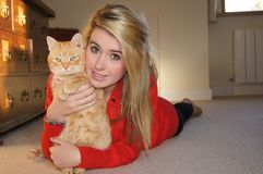 Pretty Girl and Cat. Pretty blonde girl holding her ginger cat Royalty Free Stock Image
