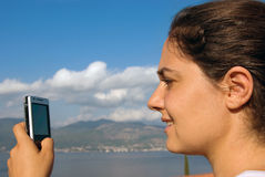 Pretty girl with cellphone at the seaside Royalty Free Stock Image