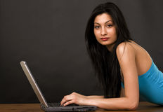 Pretty girl chatting on internet. Horizontal image on dark background Royalty Free Stock Image