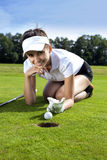 Pretty girl cheating on golf field. Tried to push the ball with her finger Stock Photos
