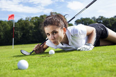 Pretty girl cheating on golf field. Tried to push the ball with her finger Stock Photography