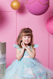Pretty girl child 4 years old in a blue dress. Baby in Rose quartz room decorated holiday. stock photography