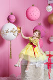 Pretty girl child 6 years old in a yellow dress. Baby in Rose quartz room decorated holiday. Stock Photos