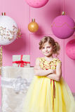 Pretty girl child 6 years old in a yellow dress. Baby in Rose quartz room decorated holiday. Royalty Free Stock Photography