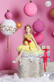 Pretty girl child 6 years old in a yellow dress. Baby in Rose quartz room decorated holiday. Stock Photo