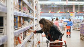 Pretty girl chooses cookies in a supermarket. Pretty curly girl in a leather jacket and red dress chooses cookies, reads the composition and puts the goods in a stock video footage