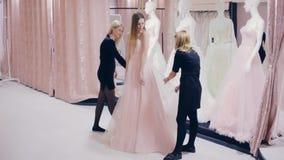 Pretty girl chooses a prom dress in shop