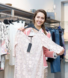 Pretty girl choosing new garment. In fashion store Royalty Free Stock Photography