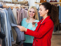 Pretty girl choosing new garment. In fashion store and smiling Royalty Free Stock Images