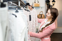 Pretty girl choosing new garment. Smiling girl choosing new garment in fashion store Royalty Free Stock Photos