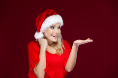 Pretty girl in Christmas cap gestures palm up Royalty Free Stock Photography