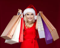 Pretty girl in Christmas cap hands packets stock images