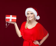Pretty girl in Christmas cap hands a present Royalty Free Stock Images