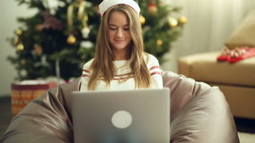 Pretty girl in christmas cap using laptop stock video