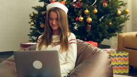 Pretty girl in christmas cap write a letter fot Santa. Portrait of pretty young girl wearing christmas cap using laptop and typing against christmas tree stock video footage